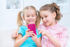 Cheerful little sisters sitting on the sofa Stock Image