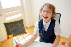 Cheerful little student bespectacled sits at school desk. It is a disciple of an elementary school. In a hand at boy ball pen. On a school desk copybooks lay Royalty Free Stock Photos