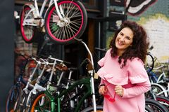 Cheerful long-haired brunette woman in a pink dress at a bicycle shop royalty free stock photography