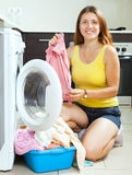 Cheerful long-haired girl doing laundry Stock Photography