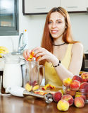 Cheerful long-haired woman cooking beverages Royalty Free Stock Photos