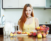 Cheerful long-haired woman cooking beverages with peaches Royalty Free Stock Photos