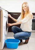Cheerful long-haired woman doing laundry Stock Image