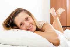 Cheerful long-haired woman  in her bed Stock Photos
