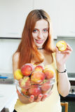 Cheerful long-haired woman holding peaches Stock Photo