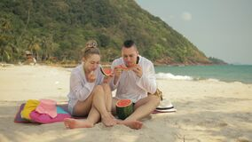 The cheerful love couple holding and eating slices of watermelon on tropical sand beach sea. Romantic lovers two people