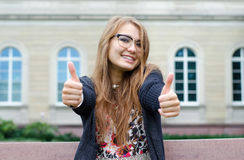 Cheerful lovely girl showing thumbs up. In the city Stock Images