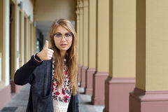 Cheerful lovely girl showing thumbs up. In the city Royalty Free Stock Photo