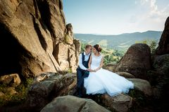 Cheerful lovely newlyweds are rubbing noses while sitting on the stone in the sunny mountains. Full-length horizontal. Wedding portrait Royalty Free Stock Photo