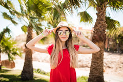 Cheerful lovely young woman in red dress and hat, sunglases walking and talking on mobile phone on summer resort Royalty Free Stock Image