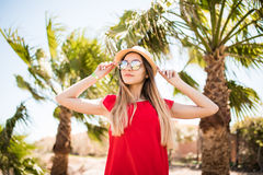Cheerful lovely young woman in red dress and hat walking and talking on mobile phone on summer resort Royalty Free Stock Photography