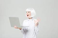 Cheerful lovely young woman standing and using laptop Stock Image
