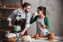 Cheerful loving couple bakers drinking coffee. Looking aside. Stock Image