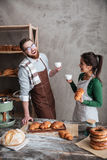Cheerful loving couple bakers drinking coffee. Looking aside. Stock Images