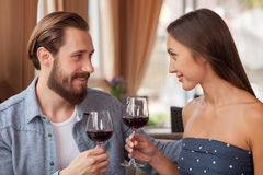 Cheerful loving couple is enjoying red drink in Stock Images