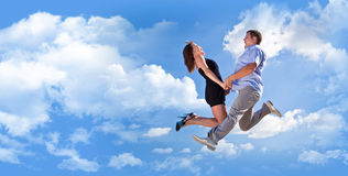 Cheerful loving couple in a jump against the blue sky Stock Image