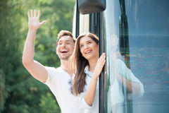 Cheerful loving couple is making fun in transport Stock Images