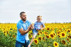 Cheerful loving father with his son on vacation in the field with sunflowers. The parent plays with his son . Father`s day stock image