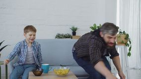 Cheerful loving father is playing with his little son throwing and kicking football and eating snacks in light apartment. Cheerful loving father is playing with stock footage