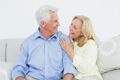 Cheerful loving senior couple sitting on sofa Royalty Free Stock Photos