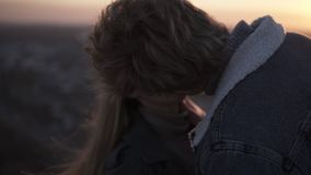 Cheerful, loving young couple enjoying a romantic kiss backlit by the sun with flare effect while standing on the windy stock footage
