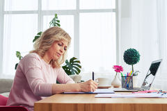 Cheerful madam of age 30-40 writing in notebook while sitting at. Side view of cheerful madam of age 30-40 writing in notebook while sitting at table stock photos