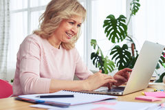Cheerful madam smiling and printing in laptop Stock Photo