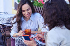 Cheerful madams surfing on Internet in smartphone over cup of te Stock Image