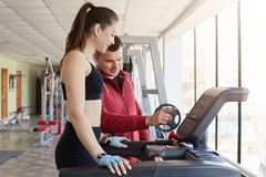 Cheerful magnetic young lady asking for help her trainer, trying to use running machine, listening to instructions carefully. Attractive girl wears black tight royalty free stock photos
