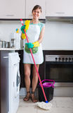 Cheerful maid cleaning at kitchen Royalty Free Stock Photos