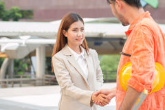 Cheerful male architect and female client are shaking hands. Stock Photography