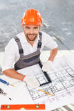 Cheerful male architect is working on project. Attractive young engineer is constructing new building. He is working with blueprint and smiling. The man is Stock Images