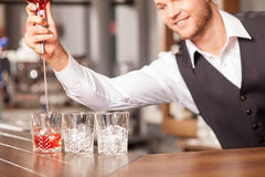 Cheerful male bartender is preparing beverage in Royalty Free Stock Images