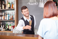 Cheerful male bartender is serving customer in bar Stock Images