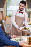 Cheerful male cafe worker is serving a customer. Attractive young waiter is holding a plate of salad and laying it on the table. He is standing and smiling. The Royalty Free Stock Images