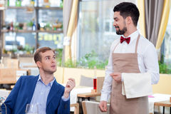 Cheerful male cafe worker is serving a customer. Attractive young waiter is receiving an order. He is standing and smiling. The businessman is sitting at the Royalty Free Stock Photos