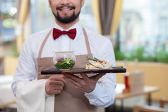 Cheerful male cafe worker is serving supper Royalty Free Stock Photo