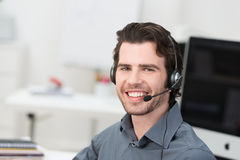 Cheerful male call centre operator. Or businessman wearing a headset sitting in an office grinning happily at the camera Stock Photography