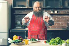 Cheerful male chef cooking healthy food. Now I will show you how to cook. Portrait of excited fat man is standing in kitchen near table with vegetables. He is Stock Photography