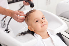Cheerful male child is having hair washed in salon. Pretty boy is getting a hairwash in beauty shop. The hairdresser is washing his head with water. The kid is Stock Images