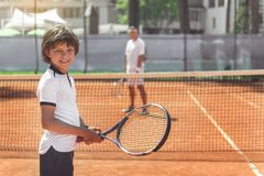 Hilarious smiling boy keeping racket. Cheerful male child is standing near net on court and looking at camera with smile. Father locating on background. Waist up Royalty Free Stock Images