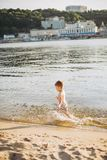 A cheerful male child of three years running along the beach near the water and splashing fly. Active Recreation In summer near th. E river Royalty Free Stock Photography
