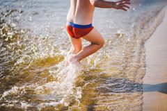 A cheerful male child of three years running along the beach near the water and splashing fly. Active Recreation In summer near th. E river Royalty Free Stock Images