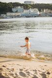 A cheerful male child of three years running along the beach near the water and splashing fly. Active Recreation In summer near th. E river Stock Image