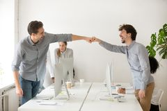 Cheerful male colleagues fist bumping celebrating successful tea. Mwork in office, friendly happy motivated coworkers excited by good work result congratulating Stock Image