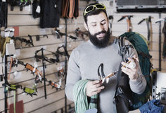 Cheerful male customer examining climbing equipment in sports eq Royalty Free Stock Photo