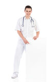 Cheerful male doctor pointing at a blank placard Stock Photos