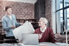 Cheerful male engineers improving blueprint Stock Photography