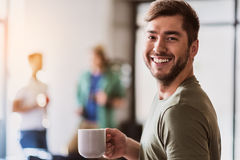 Cheerful male freelancer drinking hot beverage. Waist up portrait of joyful young men making coffee break in office. He is holding mug and laughing Stock Photo