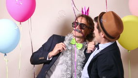 Cheerful male friends dancing in photo booth. Two cheerful male friends having fun dancing in photo booth stock footage
